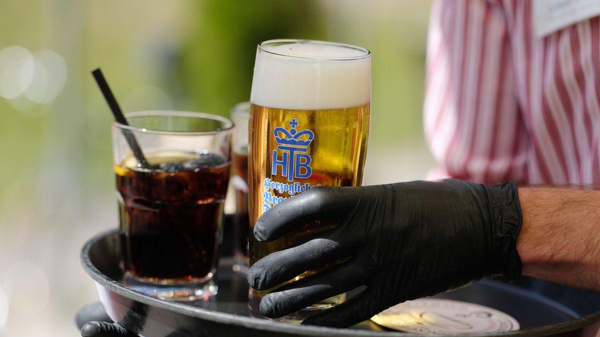 Ein Kellner arbeitet in einem Biergarten und trägt dabei Gummihandschuhe.