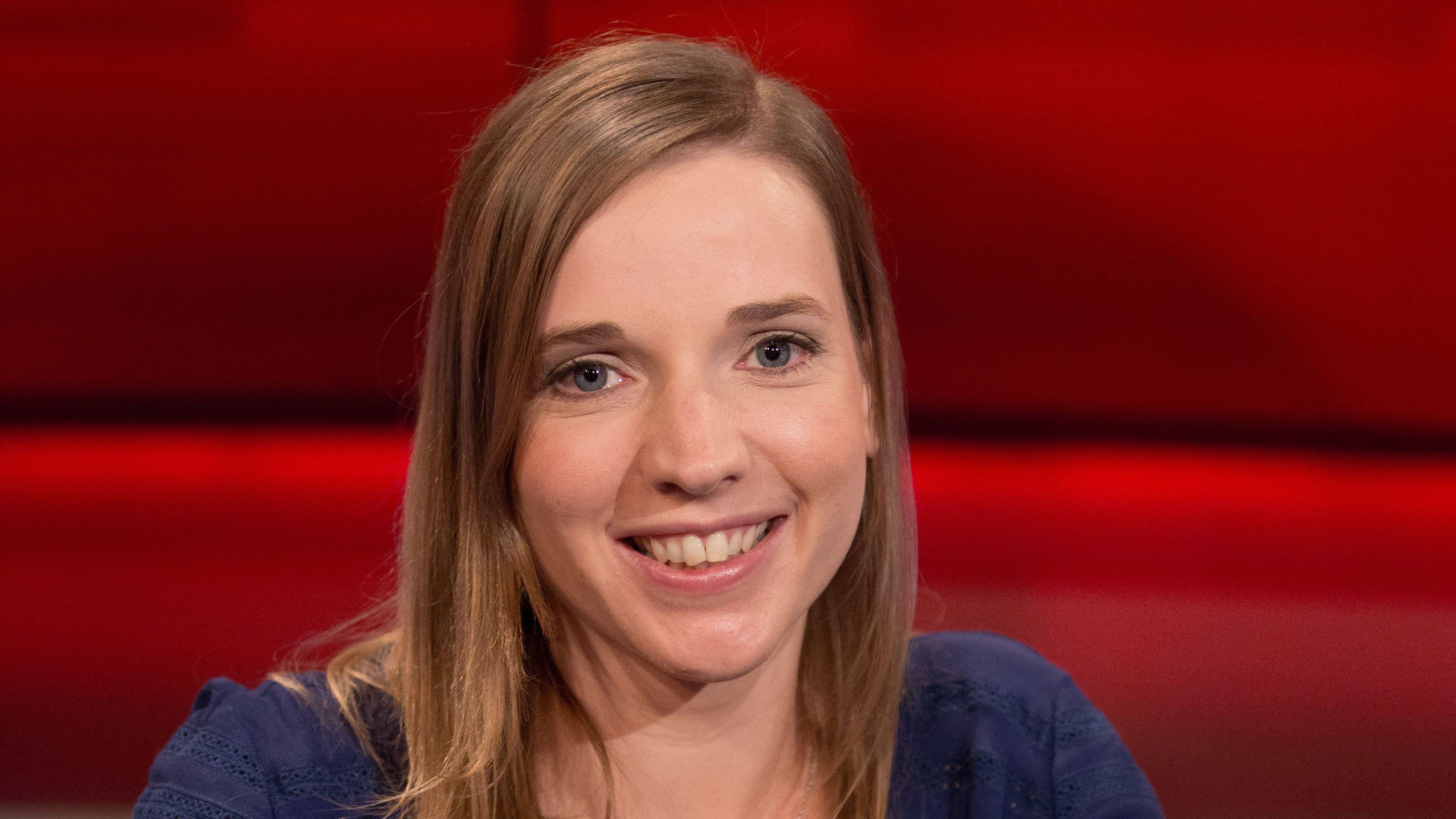 Anne Wizorek sitzt vor einer roten Wand und blickt lächelnd in die Kamera