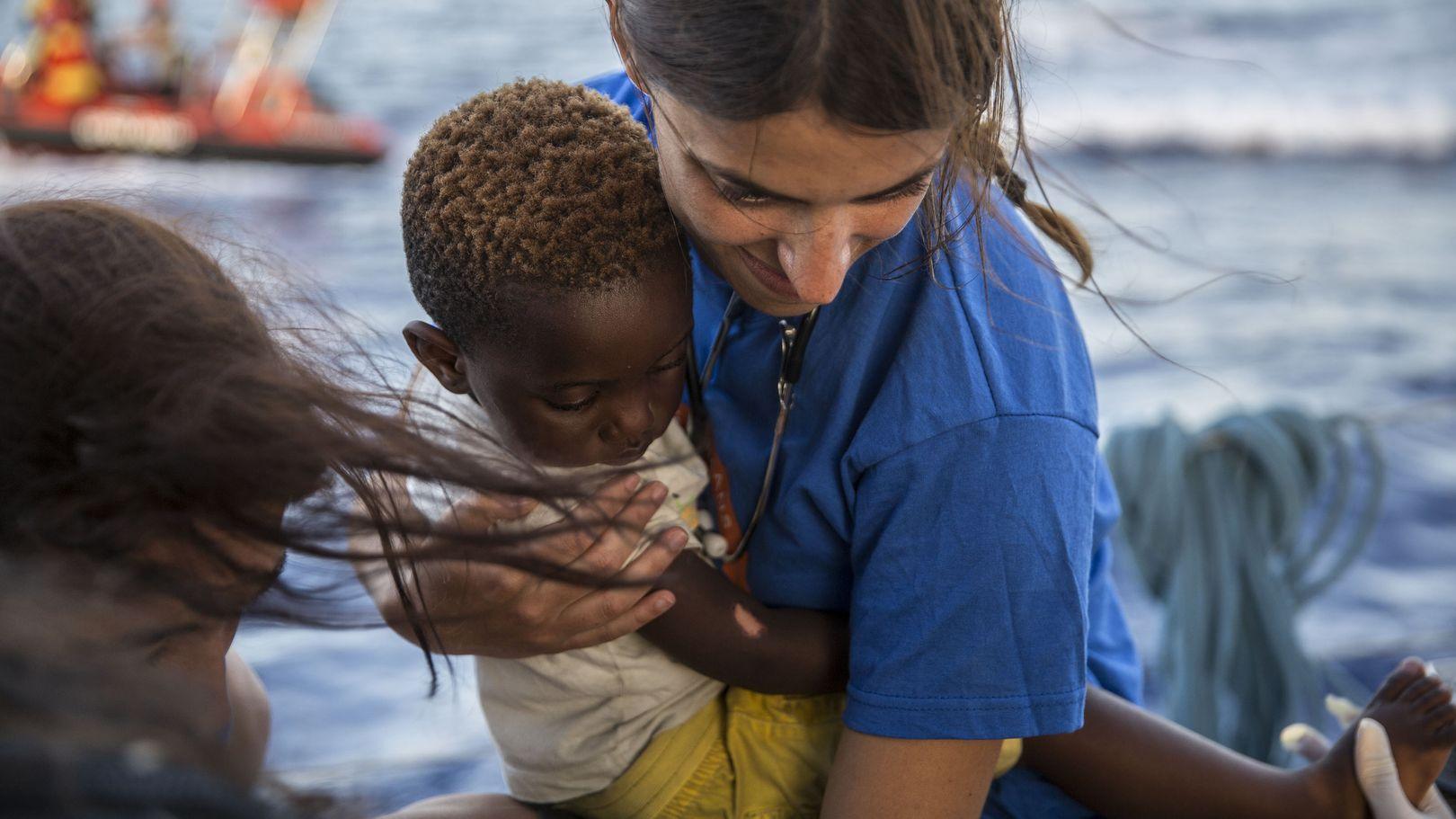 Im Mittelmeer hält am 4. Juli eine Mitarbeiterin der Hilfsorganisation Mediterranea Saving Humans einen kleinen Jungen im Arm.