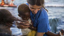 Im Mittelmeer hält am 4. Juli eine Mitarbeiterin der Hilfsorganisation Mediterranea Saving Humans einen kleinen Jungen im Arm. | Bild:dpa-Bildfunk