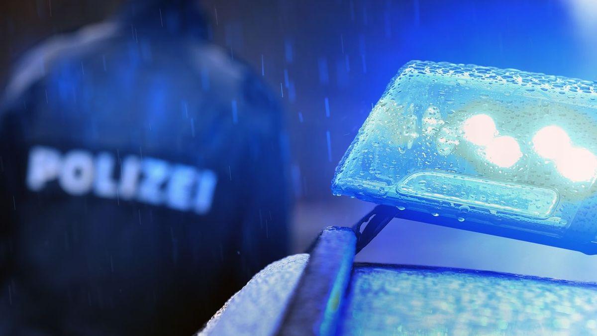 """Das Blaulicht auf einem Polizeiauto - im Hintergrund ist unscharf eine Person, auf deren Jackenrückseite """"Polizei"""" steht. (Symbolbild)"""