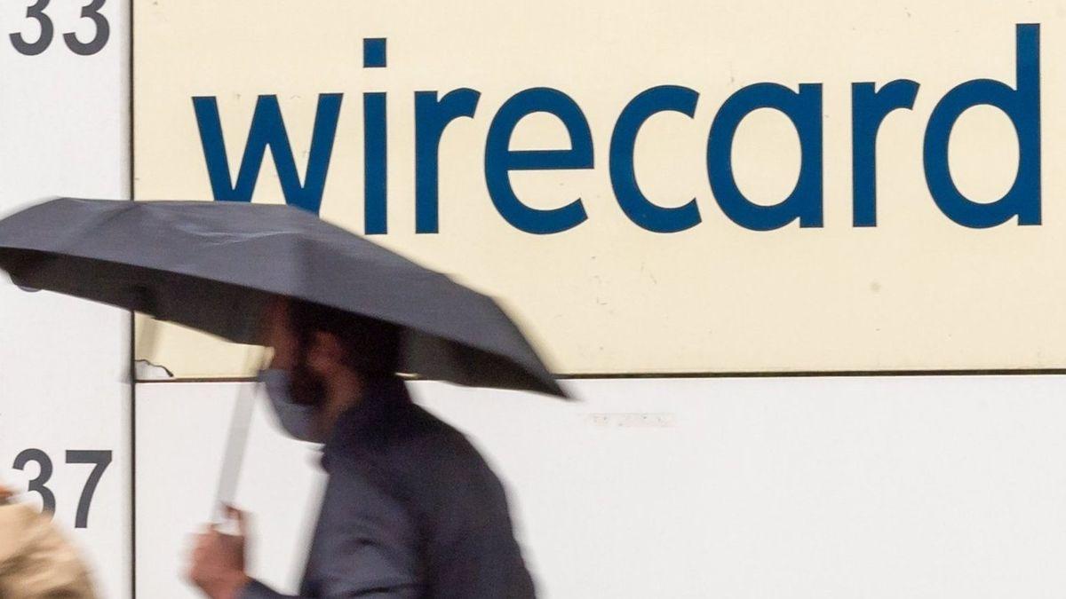 Ein Mann mit Regenschirm und Mundschutz geht an einem Wirecard-Schriftzug vorbei.