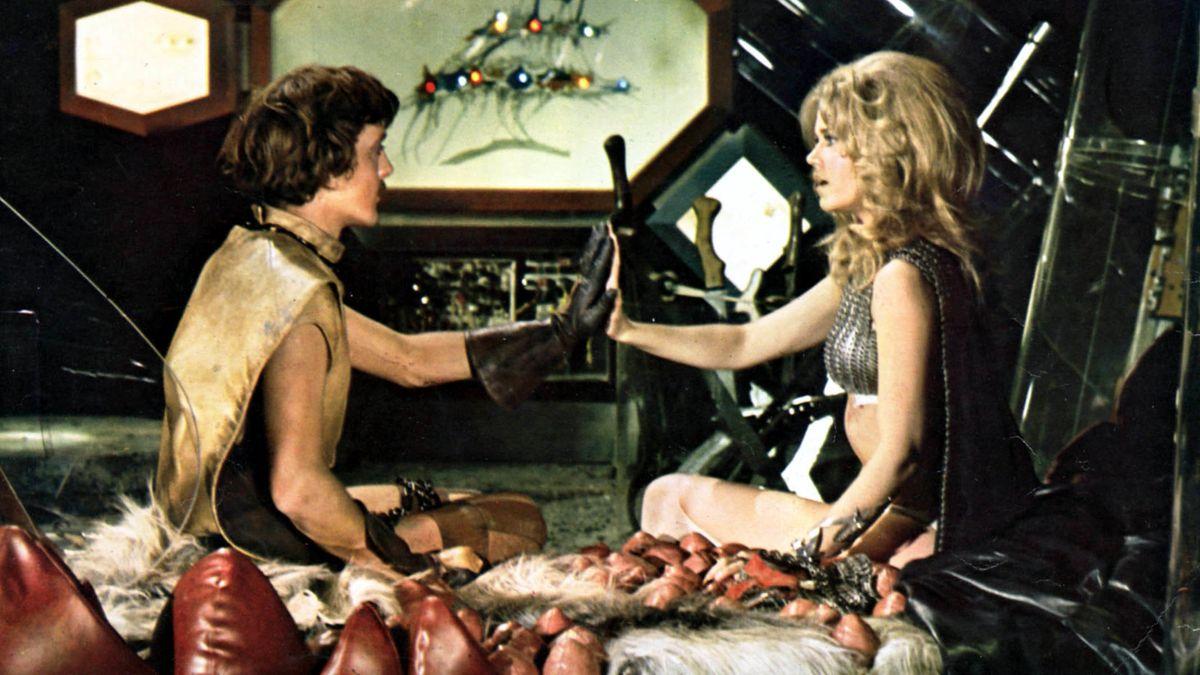 """Stars Jane Fonda (rechts) und David Hemmings (links) sitzen voreinander und legen die Hände aneinander (Szene aus dem Film """"Barbarella"""")"""