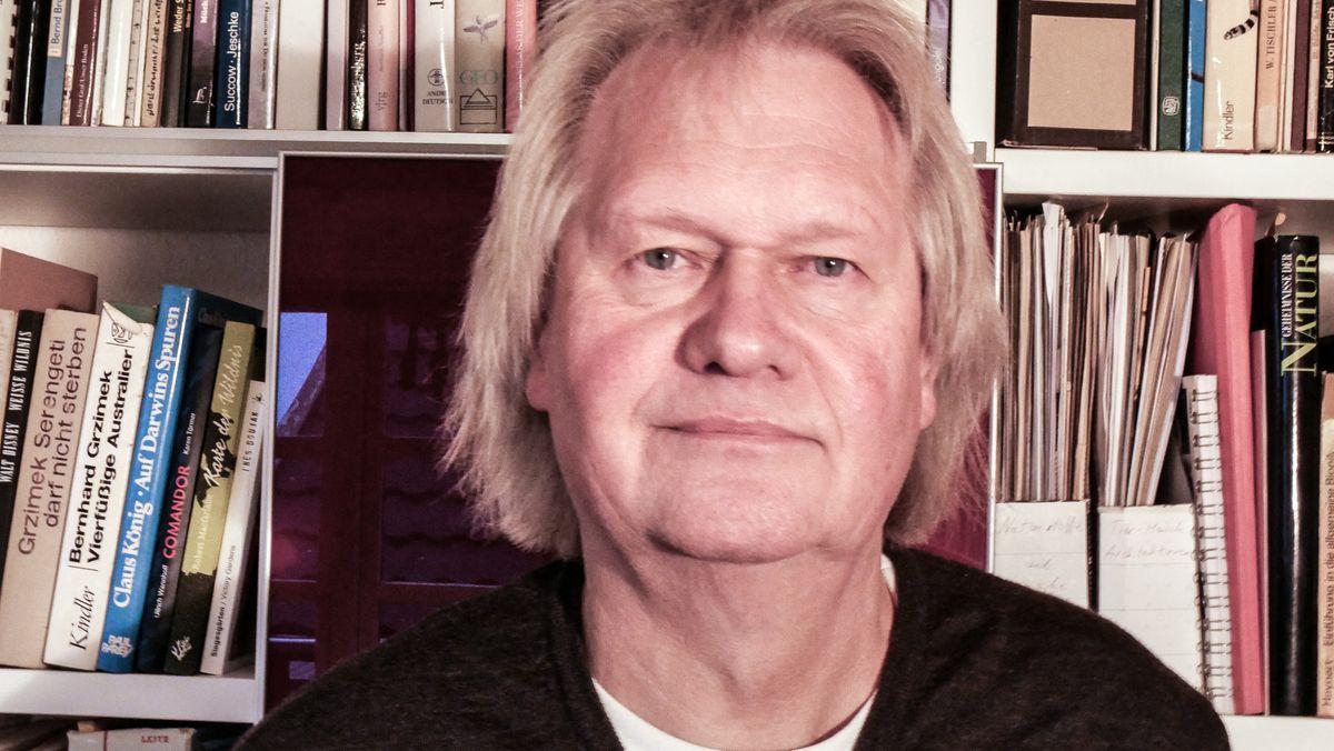 Porträt eines Mannes vor einem Buchregal