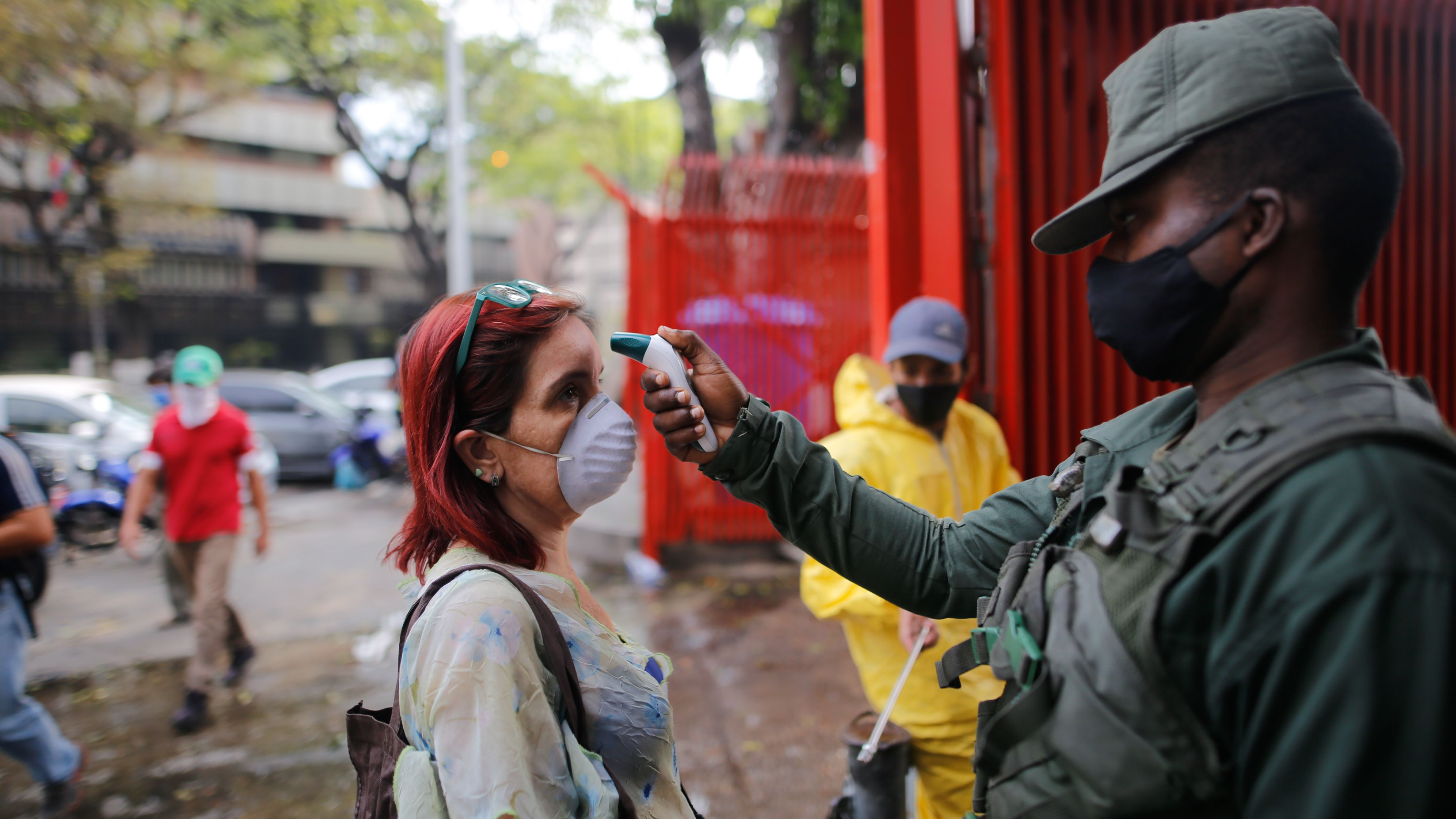 Venezuela, Caracas: Ein Soldat misst die Temperatur bei einer Frau am Eingang eines Marktes als Maßnahme gegen die Ausbreitung des Coronavirus.