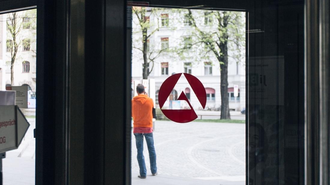 Ein Mann steht vor der Agentur für Arbeit.