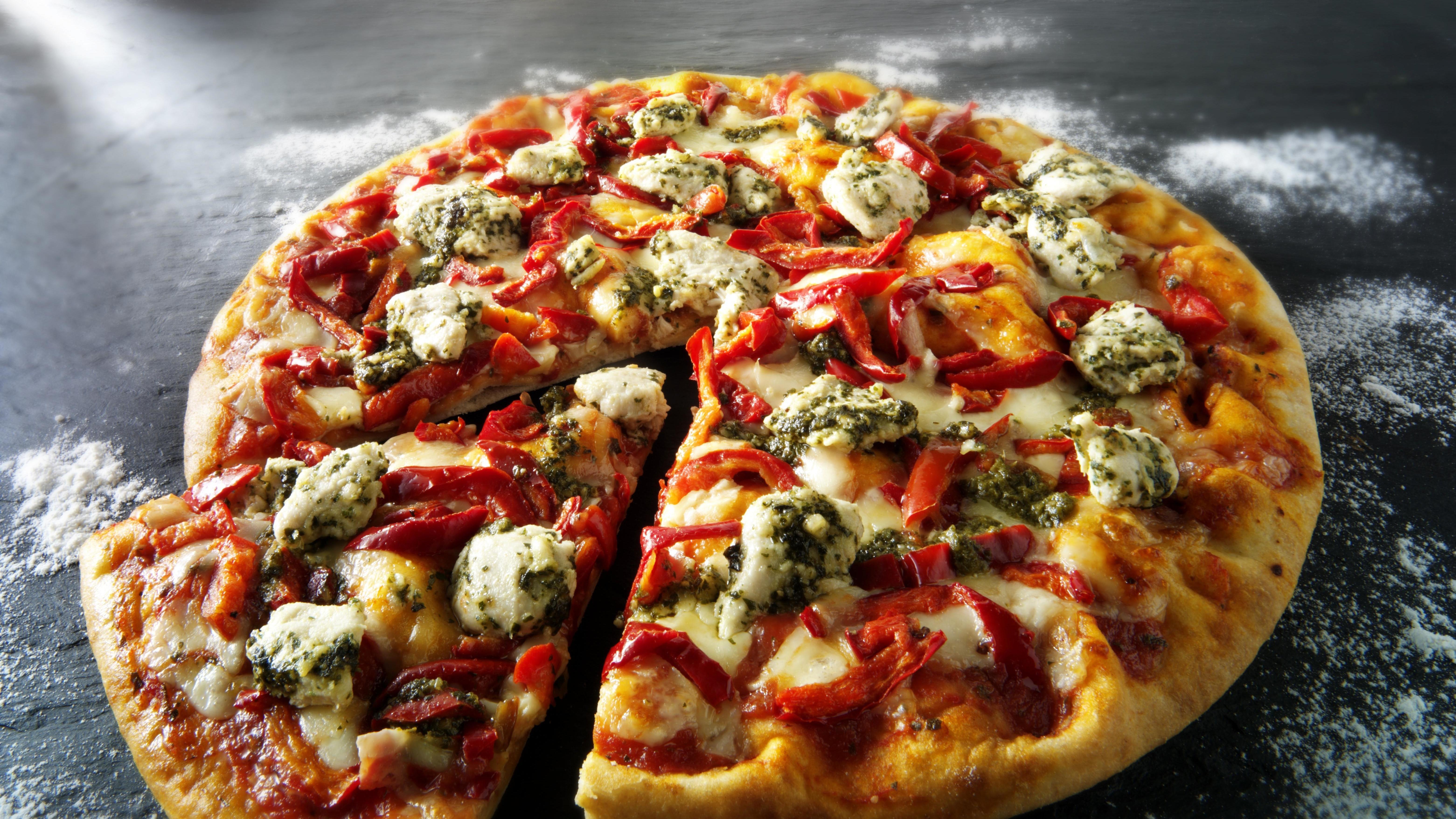 Eine aufgebackene Pizza liegt auf einem Tisch. Ein Stück ist abgeschnitten.