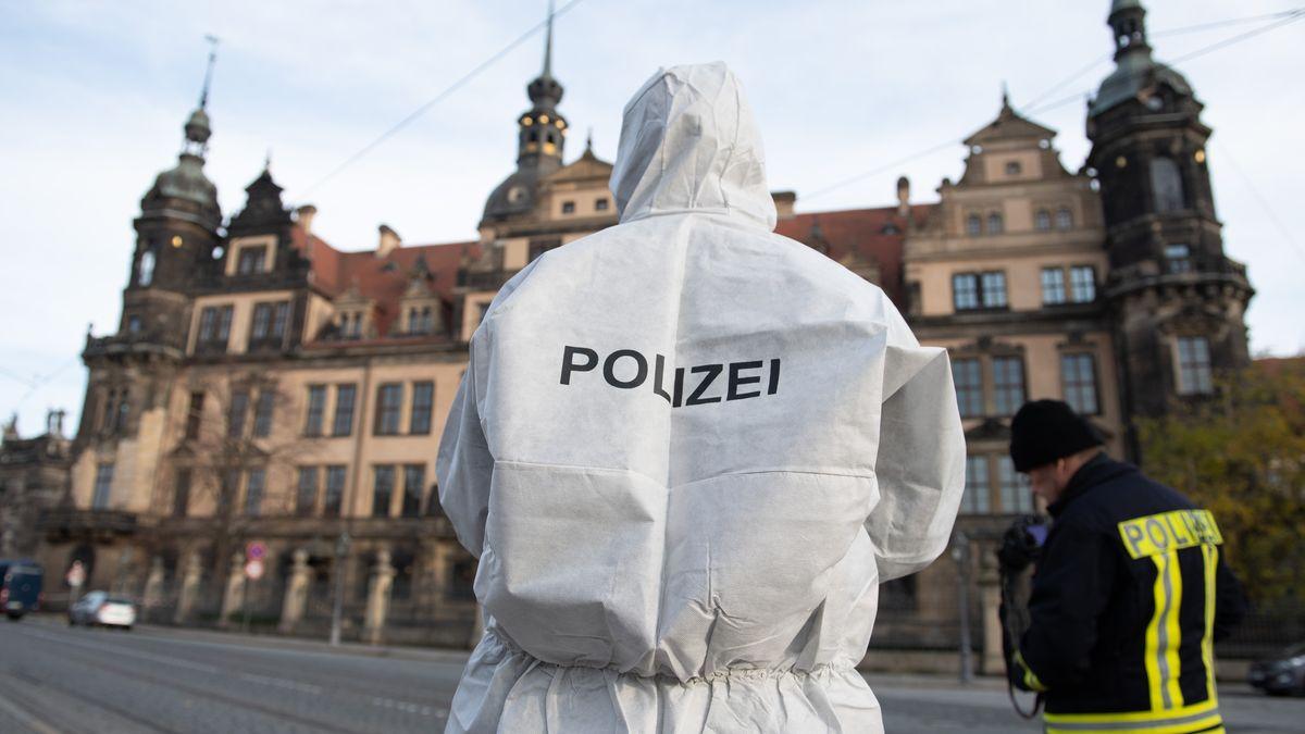 Zwei Polizisten mit weißen Schutzanzug und Uniform vor dem Residenzschloss mit dem Grünen Gewölbe in Dresden.