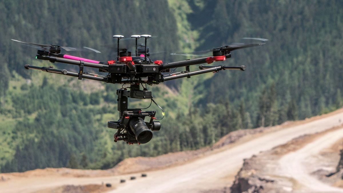 Drohne fliegt über eine neu angelegte, schotterbraune Bergstraße, im Hintergrund Bergwald