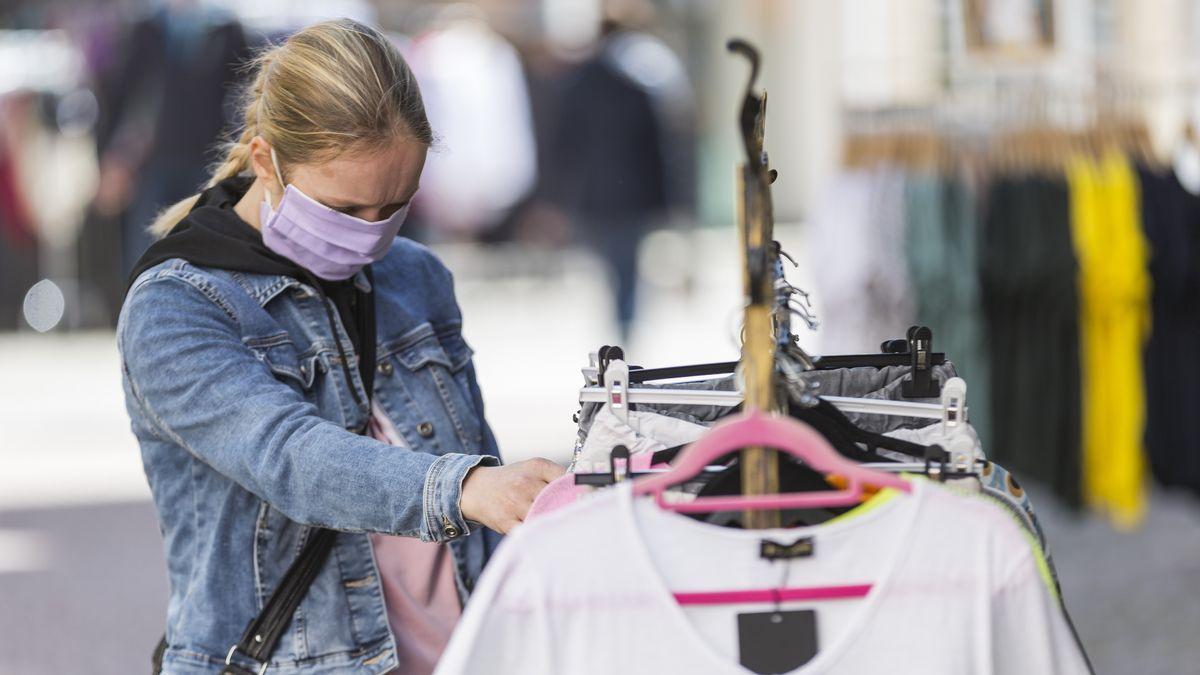 Eine Frau mit Maske schaut sich Kleider vor einem Geschäft an (Symbolbild).