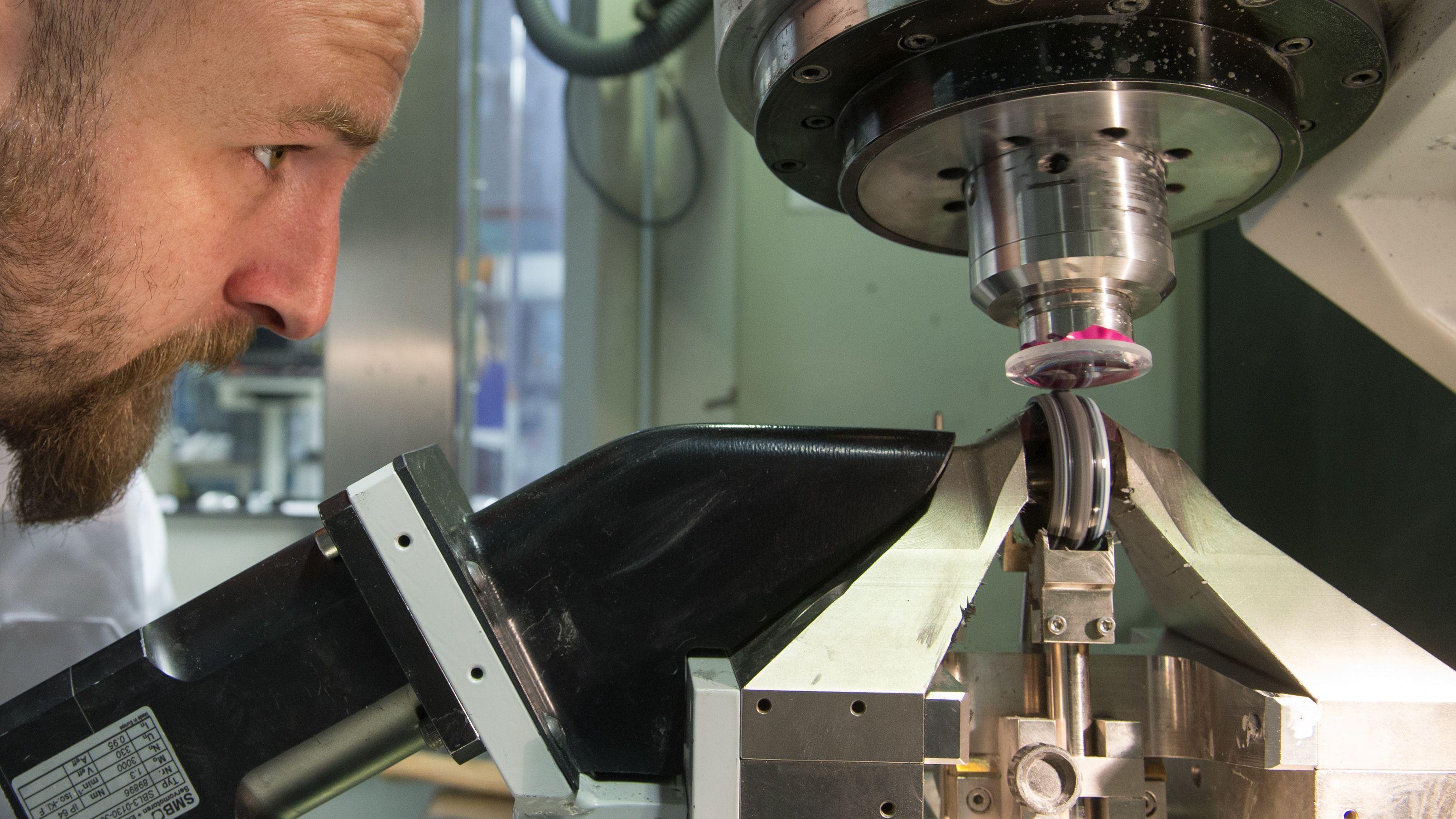 Im Technologiecampus Teisnach beobachtet ein Student wie eine Glaslinse mit einer Maschine bearbeitet wird