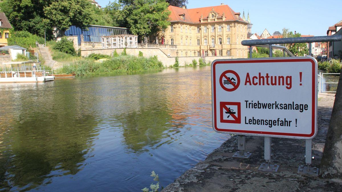 """Ein Badeverbots-Schild am Ufer der Regnitz unter anderem mit der Aufschrift """"Lebensgefahr""""."""