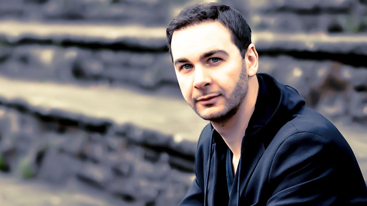 Autor Pierre Jarawan blickt, auf einer Treppe im Freien sitzend, in die Kamera