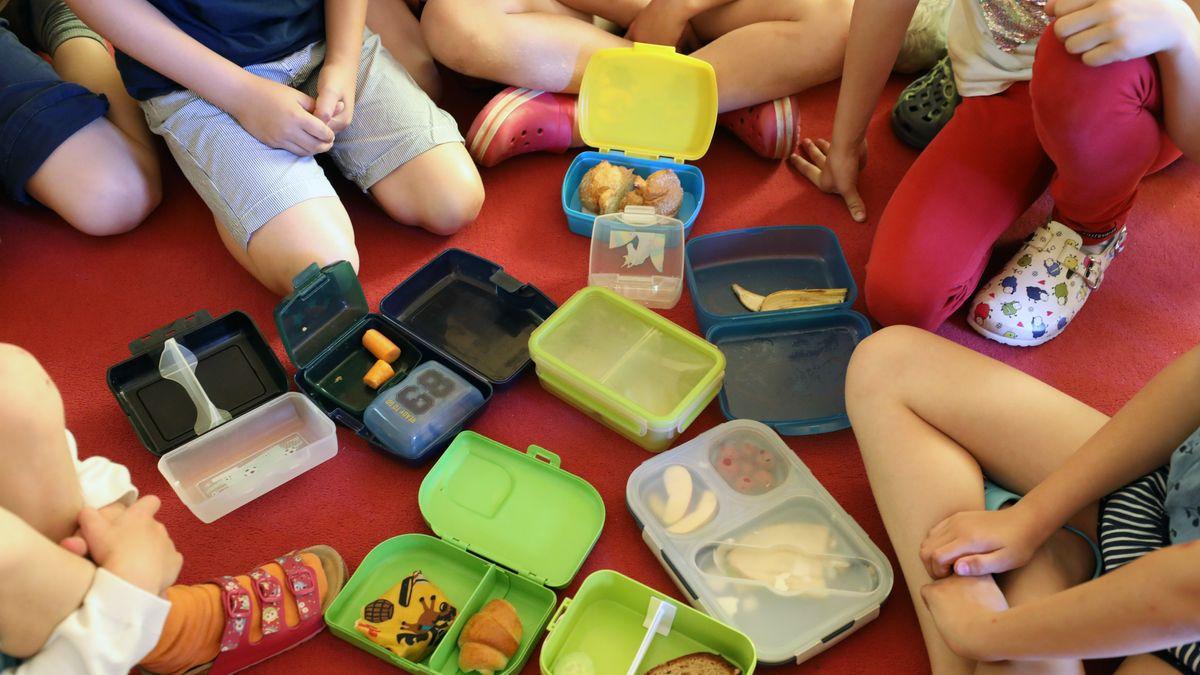 Schülerinnen und Schüler mit Brotdosen aus Plastik.