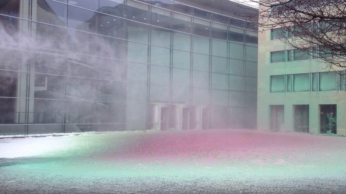 Bunter rauchender Kunstschnee liegt auf einem Platz. Dahinter erhebt sich das Neue Museum in Nürnberg.