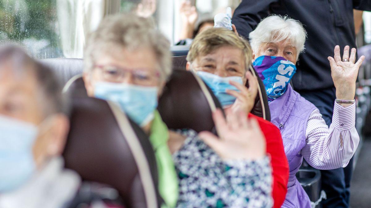Senioren mit Mundschutz in einem Bus