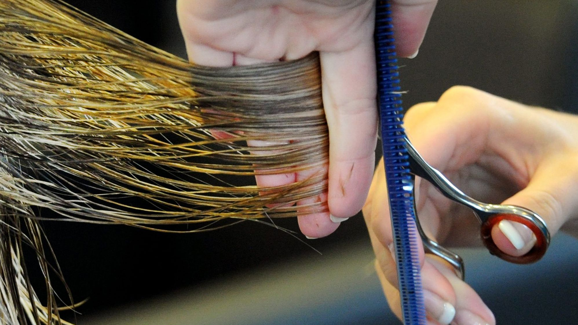Friseurin schneidet einer Kundin die Haare