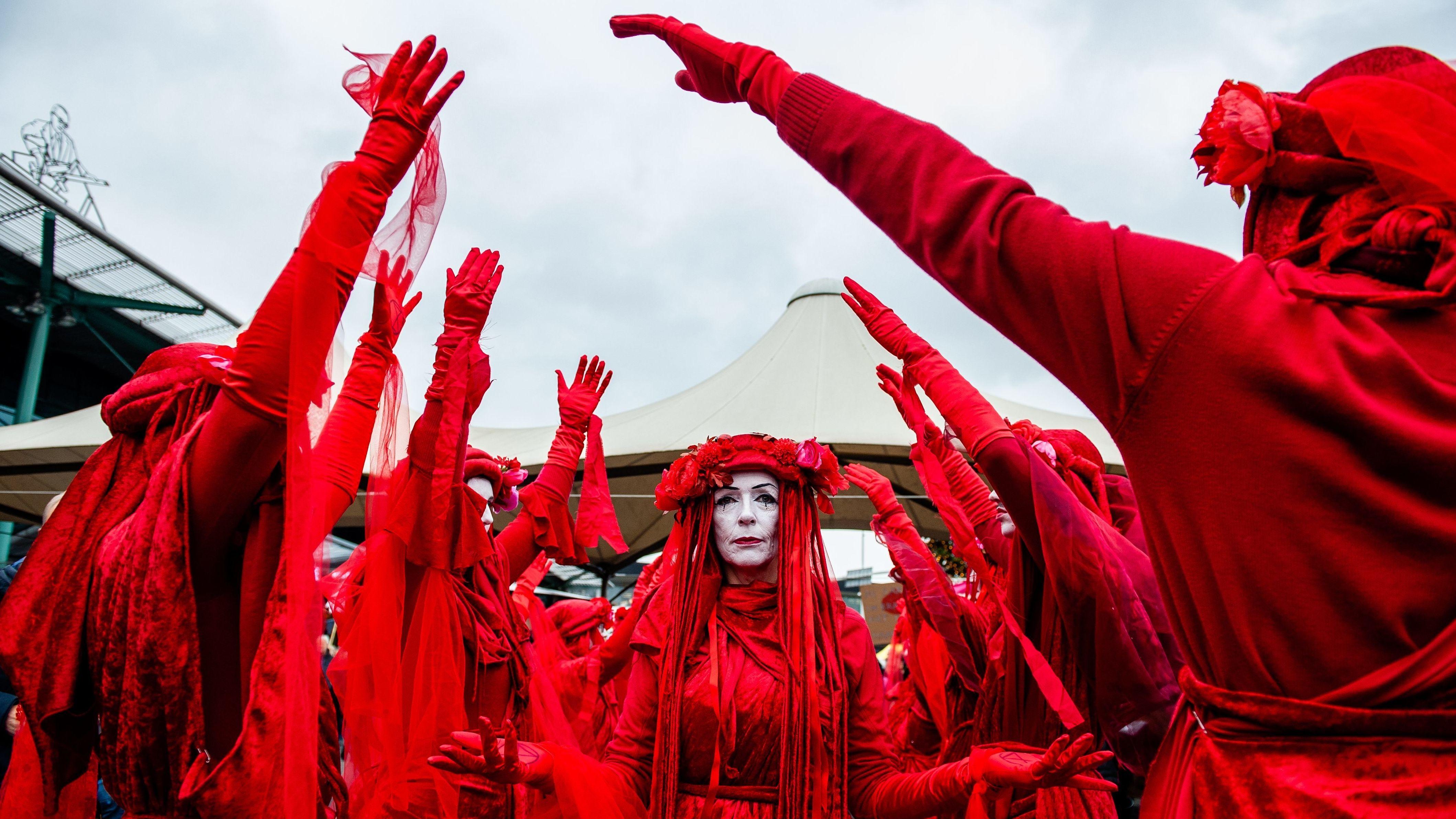 """Rotgekleidete und weiß geschminkte Aktivisten bei einer Protest-Choreografie gegen den Klimwandel: """"Extinction Rebellion"""" bei einer Aktion am Amsterdamer Flughafen Schiphol (Dezember 2019)"""
