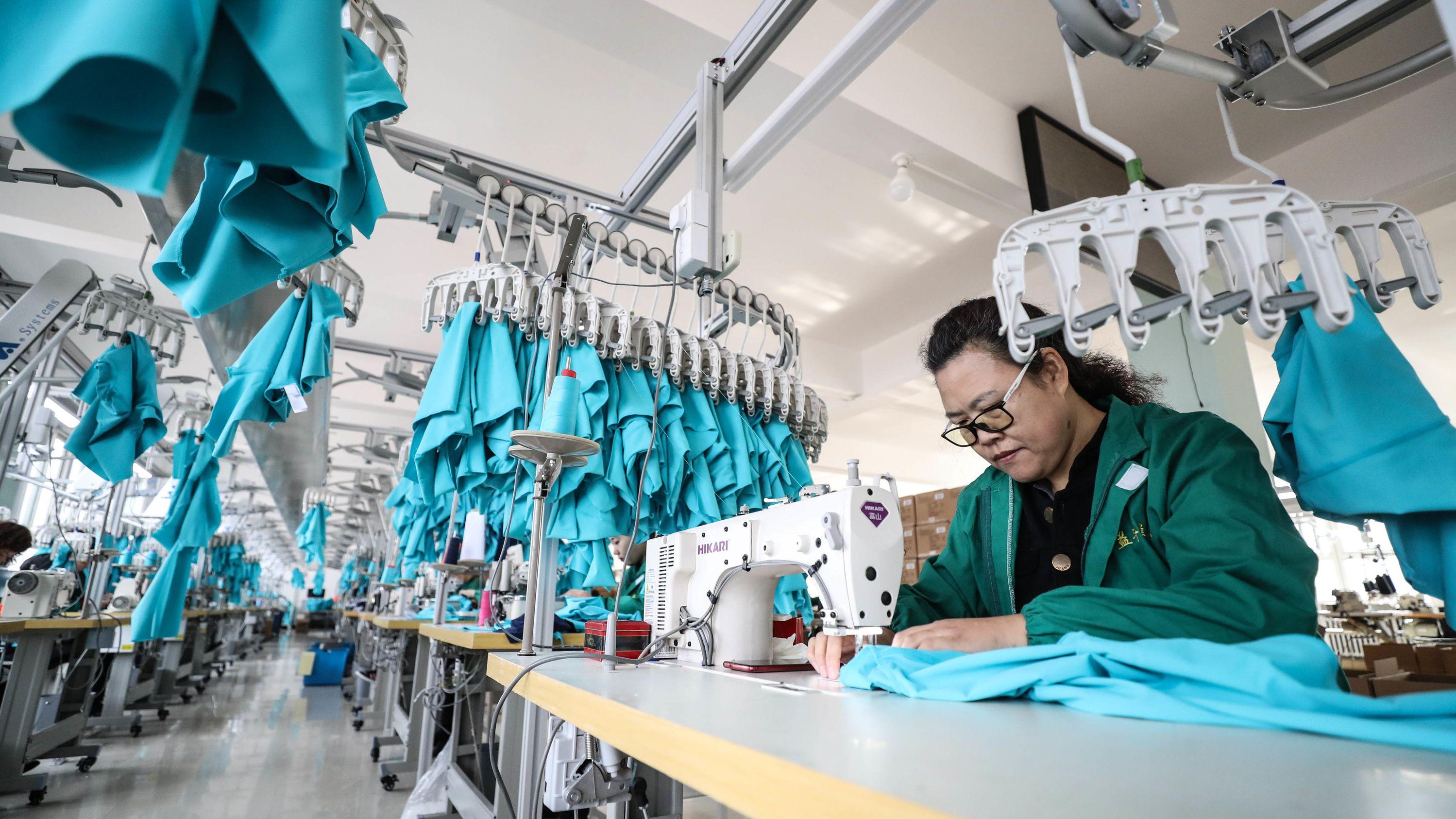 Eine Näherin arbeitet an ihrer Nähmaschine in der Fabrik Sportbekleidungsunternehmens.