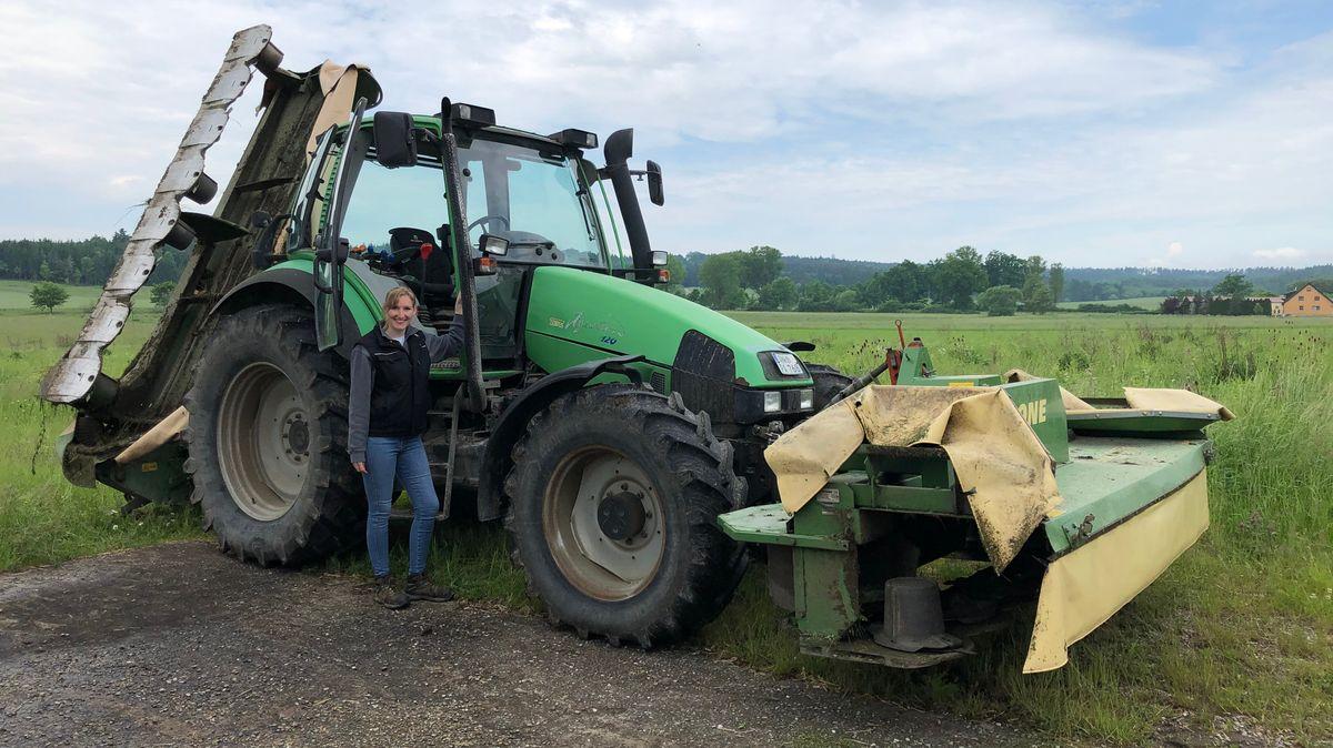 Landwirtin Laura Winhart steht vor ihrem Traktor mit Mähwerk und wartet auf die Freigabe nach erfolgreicher Absuche nach Tieren auf ihrer Wiese