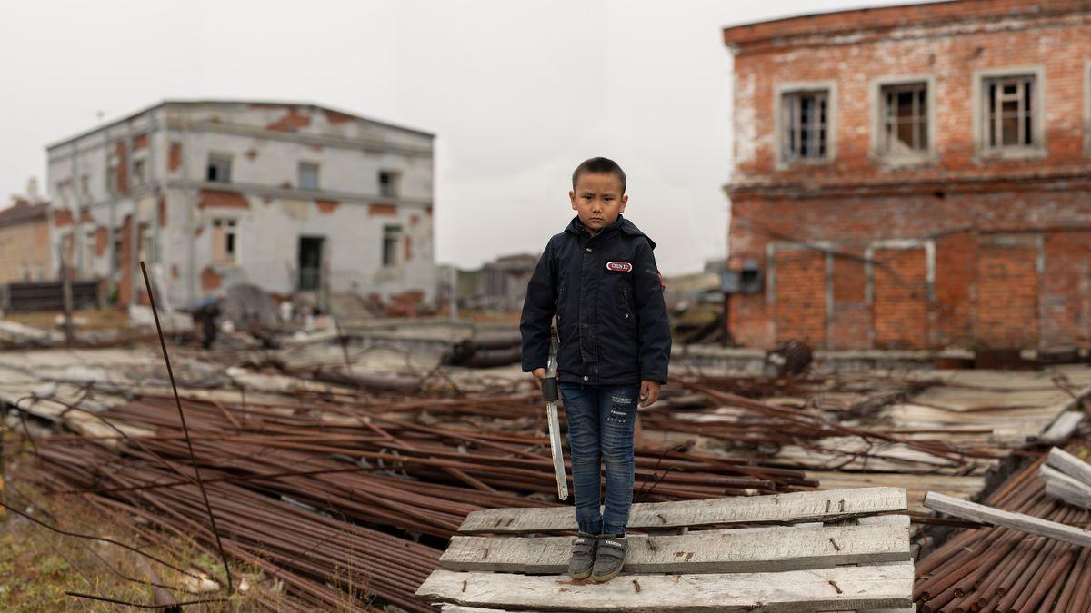 Ein vielleicht sechsjähriger Junge mit Schwert auf einer Bauhalde, dahinter Ruinen von Häusern