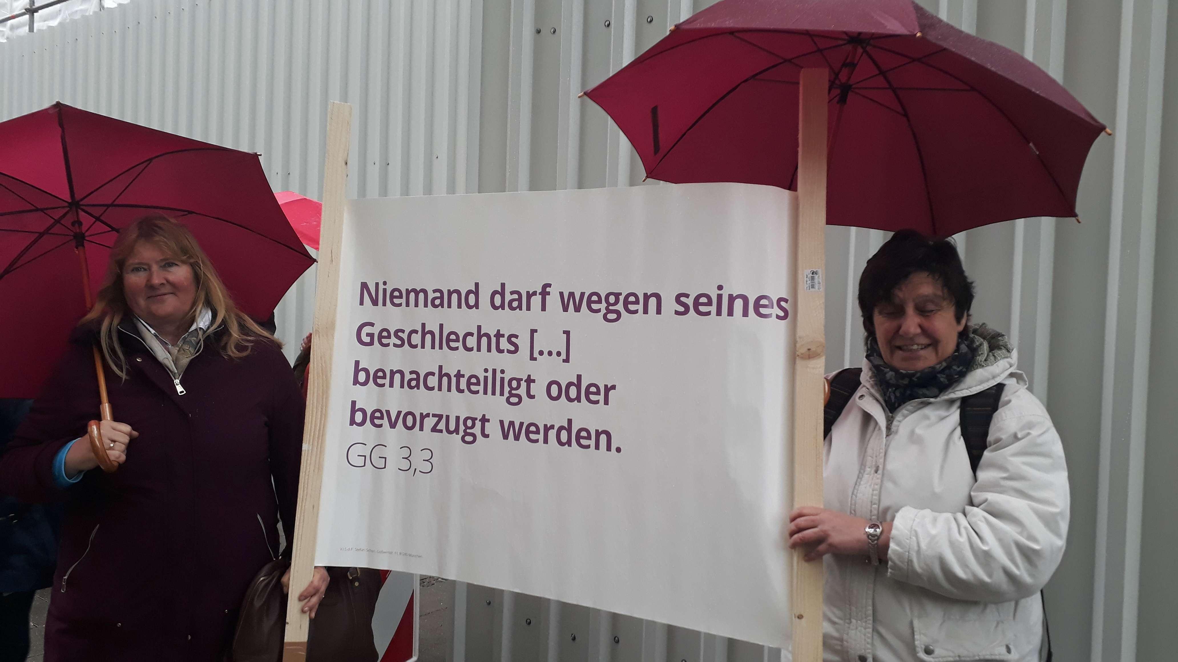 Zwei Demonstrantinnen mit einem Plakat
