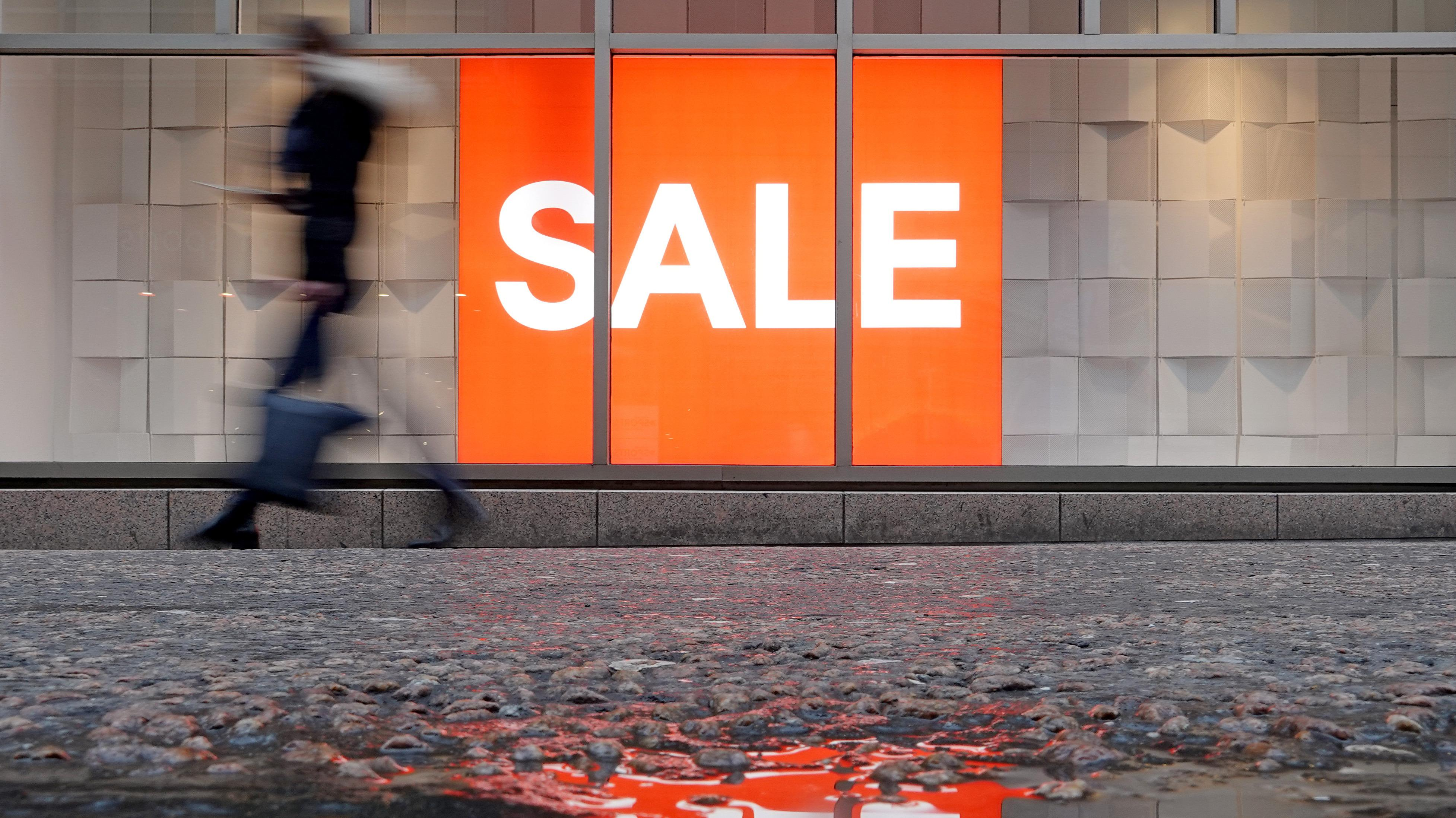 Eine Frau geht vor einem Schaufenster mit Sale-Schild vorbei