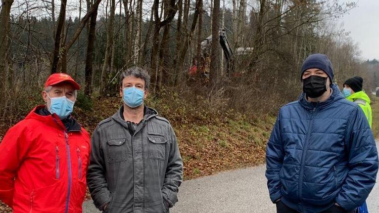 Drei Mitglieder der Bürgerinitiative Wasserburger Land mit Mund-Nasen-Masken stehen vor einem Waldstück, in dem ein Bagger mit Rodungsarbeiten begonnen hat.