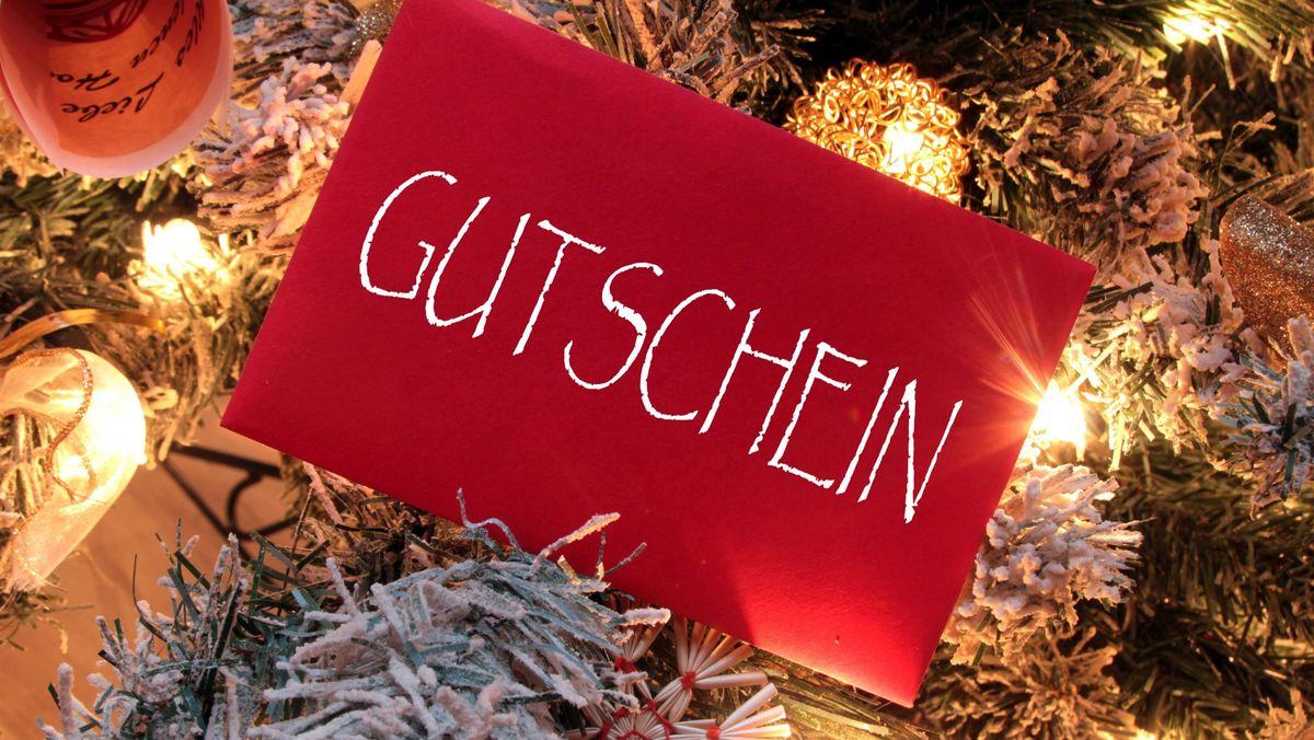 Gutschein im roten Briefumschlag vor weihnachtlicher Dekoration