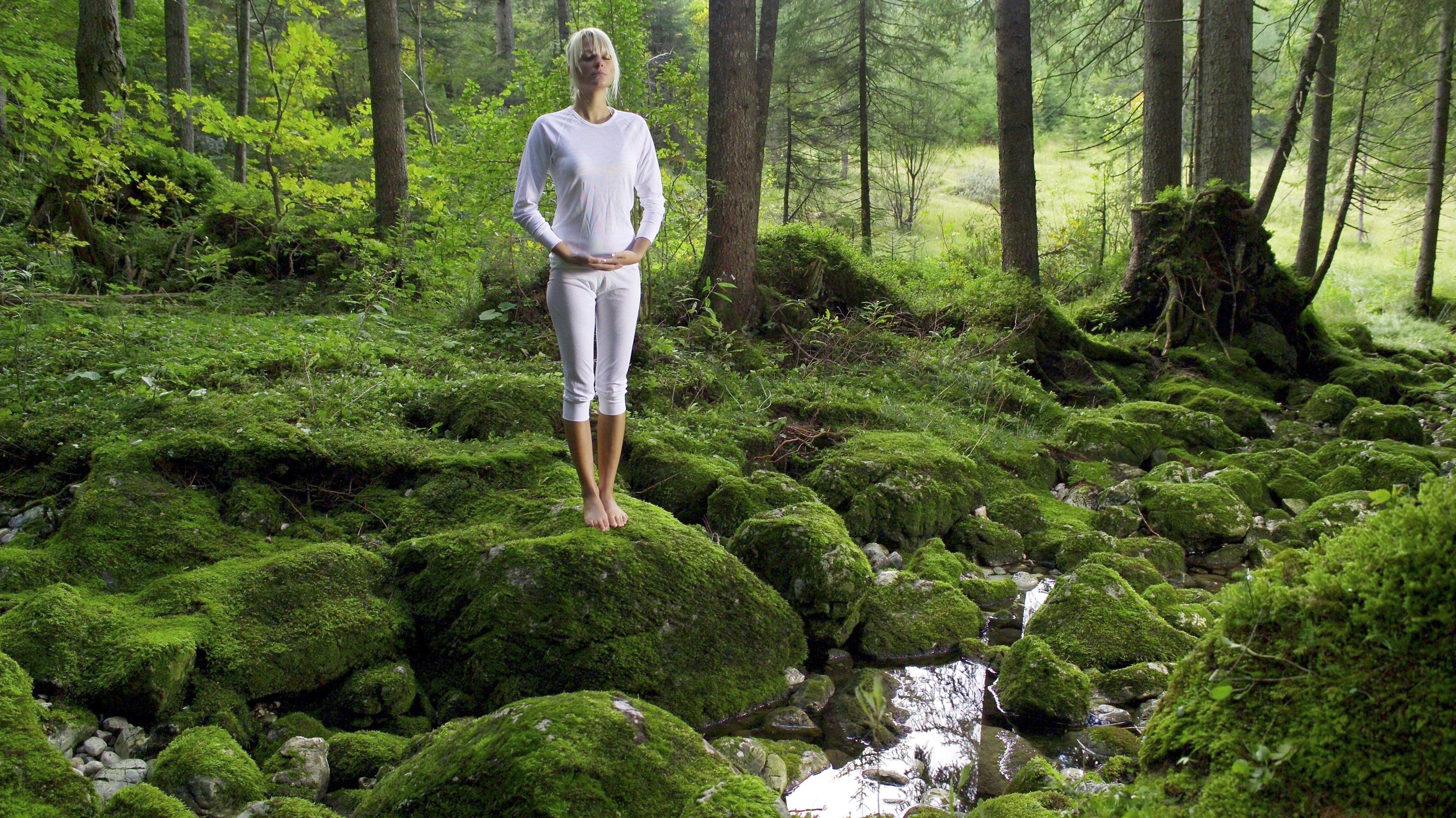 Frau meditiert im Wald