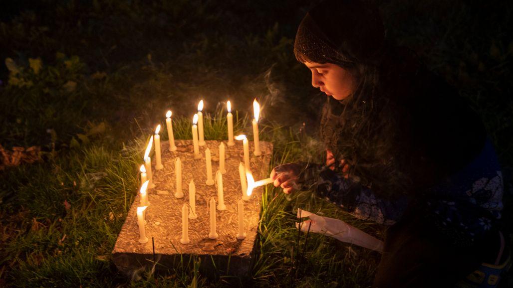 Ein muslimisches Mädchen zündet am Grab ihres Verwandten Kerzen an.