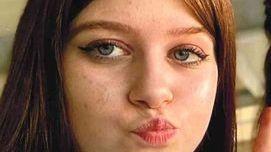 Bild eines Mädchens mit langen Haaren und Sommersprossen.