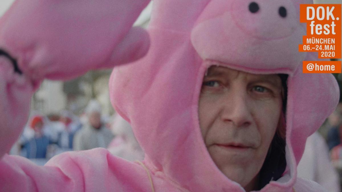Ein Mann in einem rosanen Schweins-Kostüm schaut unter der Schweismaske hervor