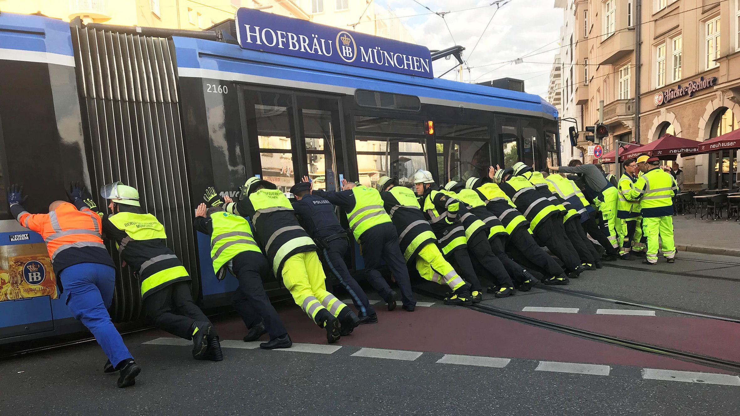 Feuerwehrmänner schieben die entgleiste Tram vom Münchner Kurfürstenplatz