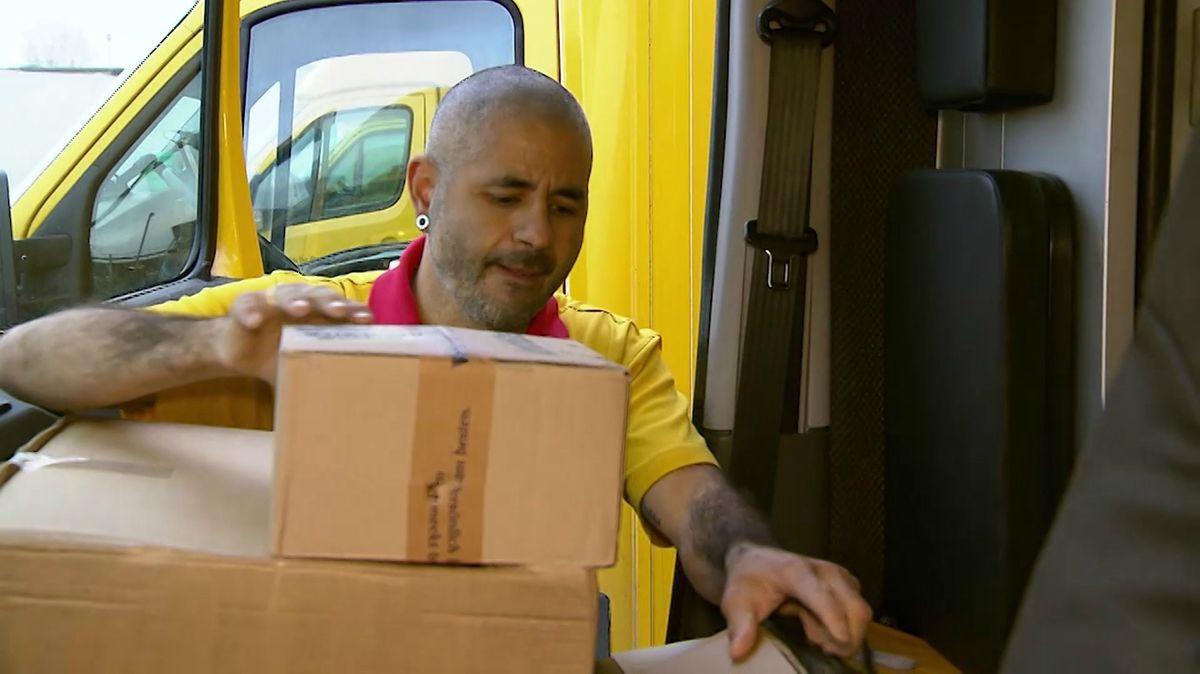 Taner Röls in DHL-Uniform belädt sein Postauto mit Paketen.