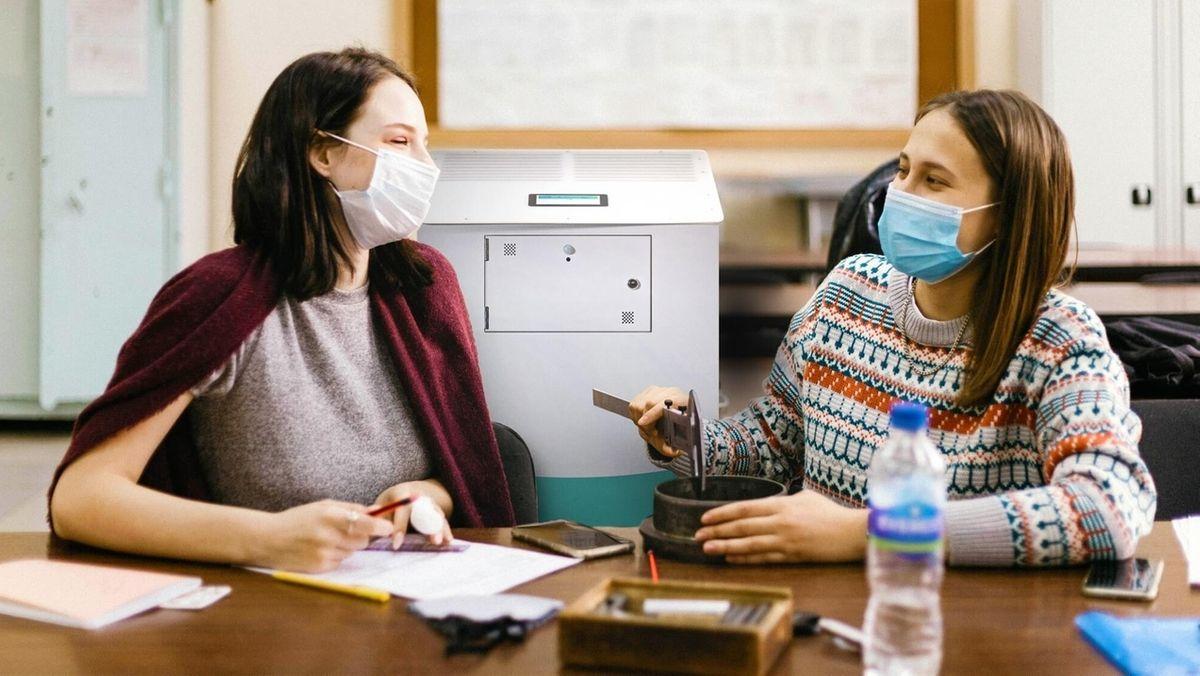 Schüler mit Masken in der Schule, im Hintergrund ein Luftreiniger.