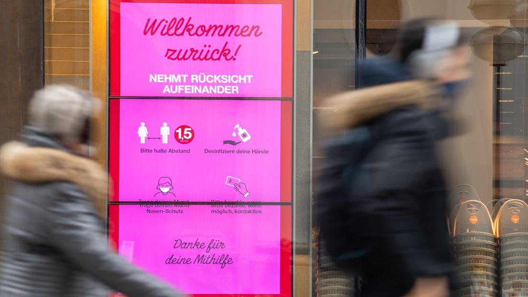 Passanten laufen durch die Münchner Innenstadt an einem Geschäft vorbei.