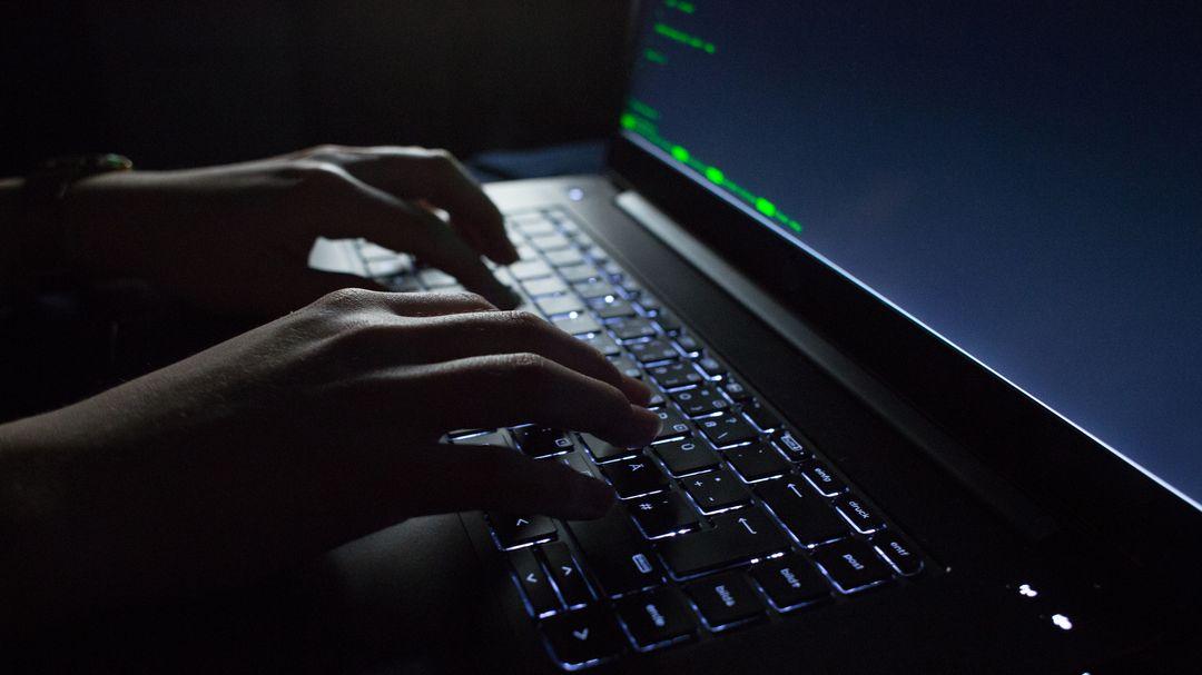 Hände tippen auf einem Laptop mit Porgrammcode auf dem Display.