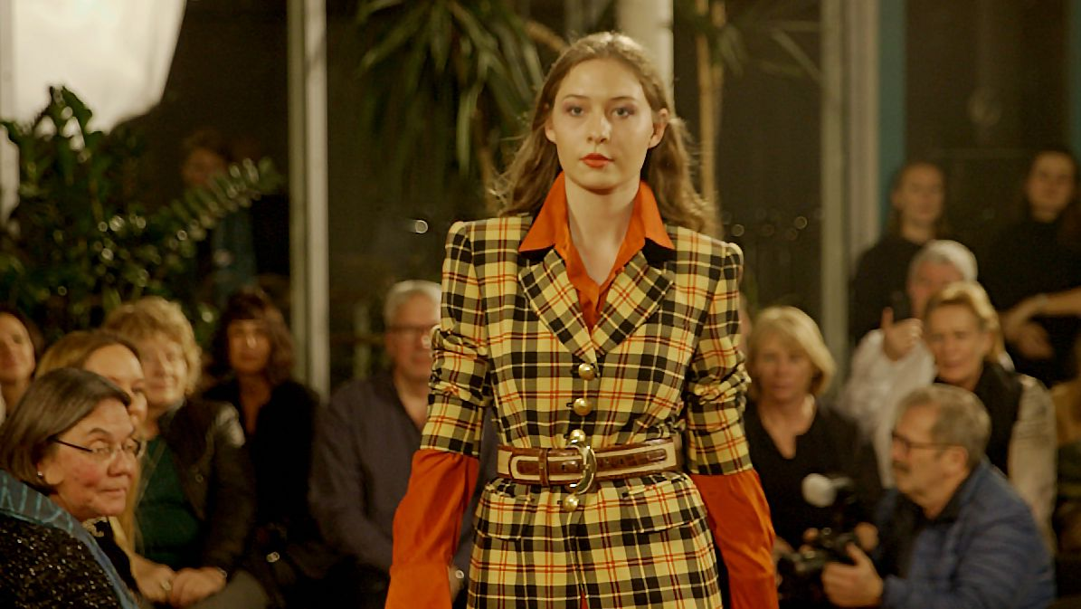 Eine junge Frau trägt einen karierten Blazer und eine orangenfarbene Bluse bei einer Altkleider-Modenschau.