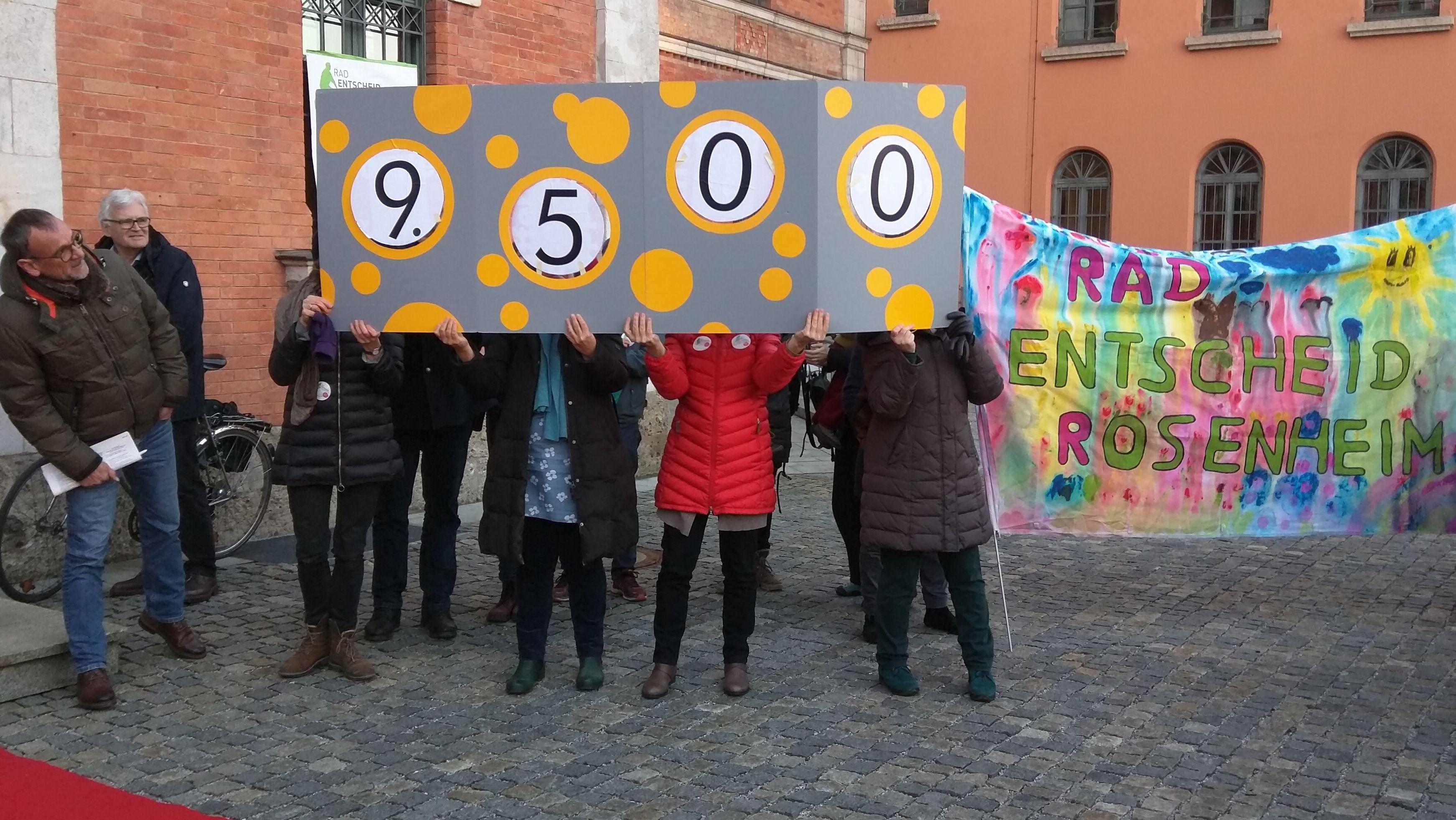 """Unterstützer des Radentscheids Rosenheim halten ein Schild mit der Zahl """"9.500"""" hoch."""