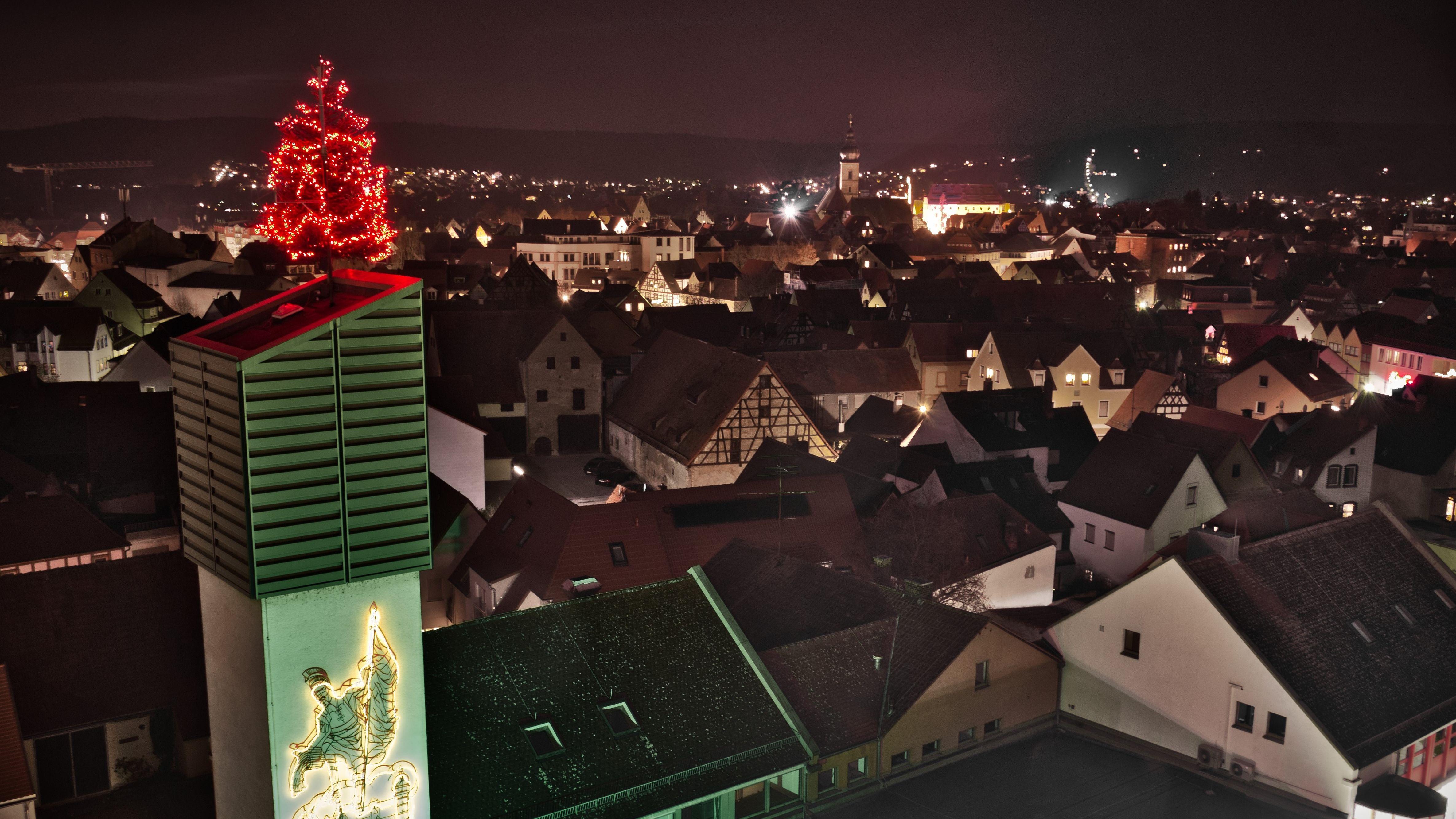 Vor der abendlichen Kulisse der Stadt Forchheim steht ein rot leuchtender Weihnachtsbaum auf dem Dach des Schlauchturms der Feuerwehr.
