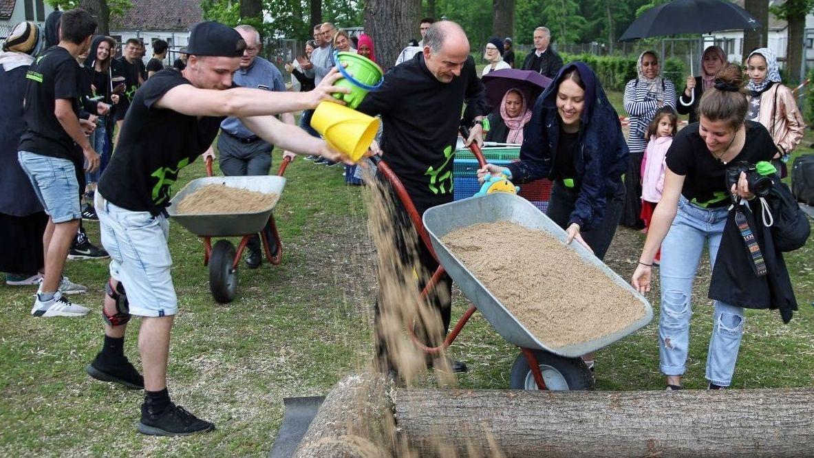 Bischof Franz Jung hilft beim Befüllen des Sandkastens in der Gemeinschaftskunterkunft in Kitzingen
