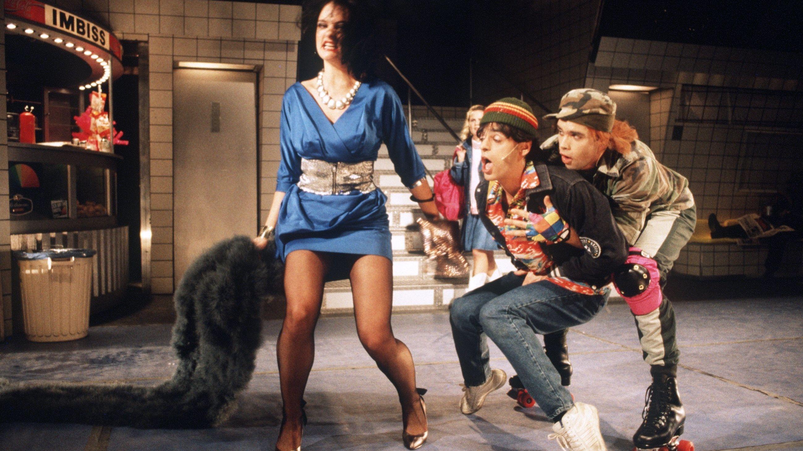 Zwei Jugendliche und eine Frau in eleganter Kleidung performen auf der Bühne.