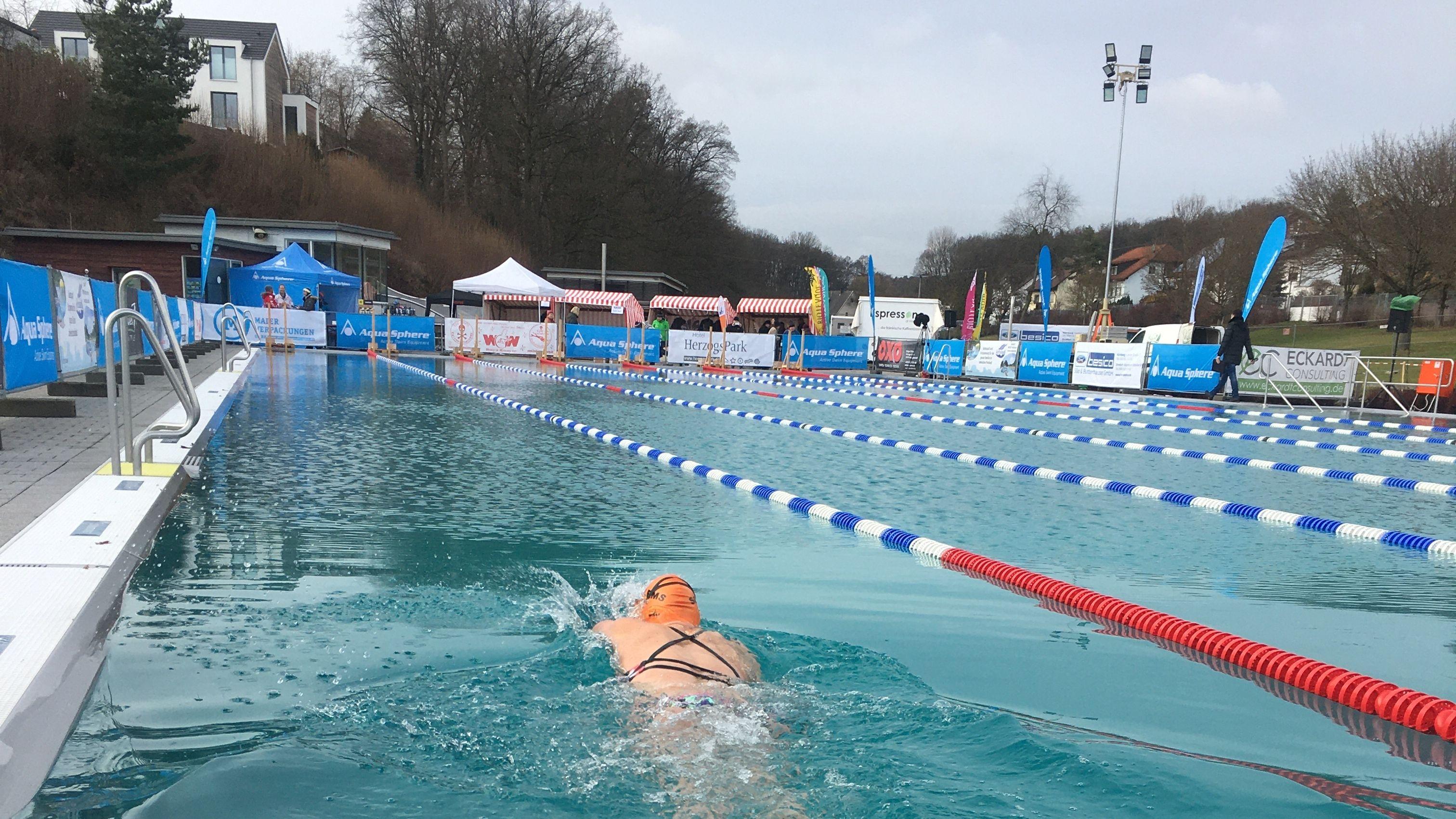 Schwimmerin in Außenschwimmbecken im Winter
