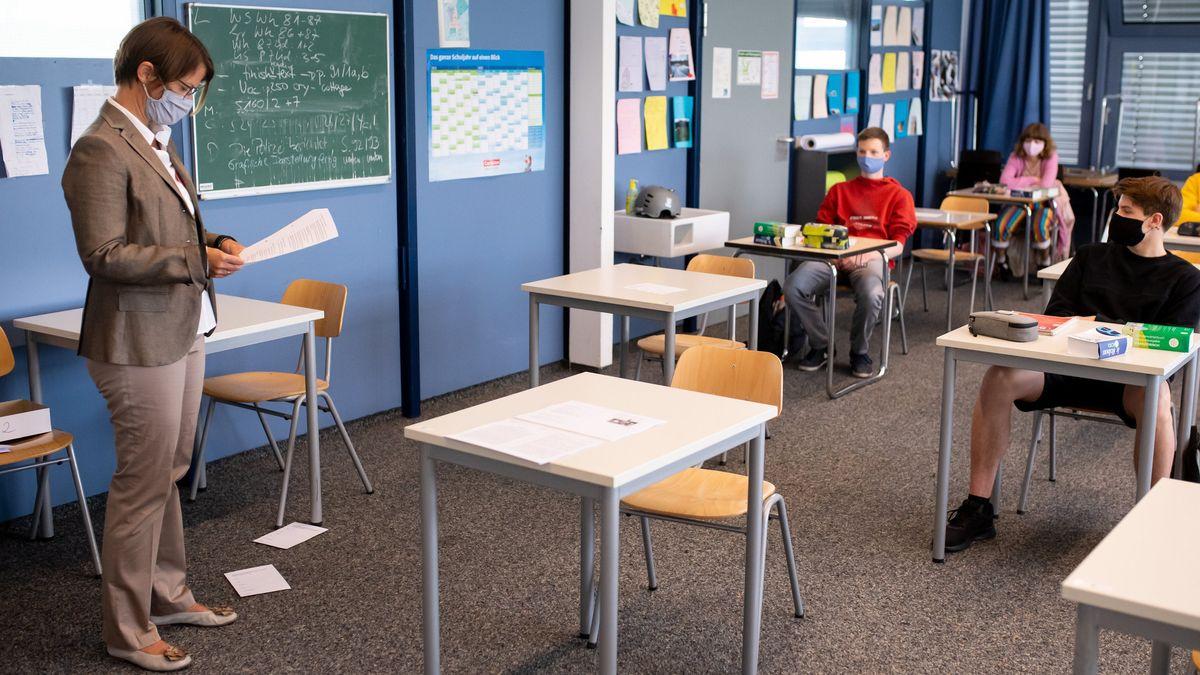 Eine Lehrerin steht im Unterricht vor Schülern und Schülerinnen in einer 12. Klasse eines Gymnasiums in Unterhaching.