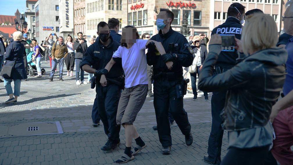 Eine Frau wird während der Kundgebung in Nürnberg von der Polizei abgeführt