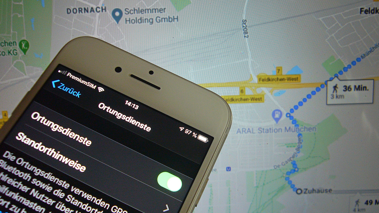 """Handyortung: Auf einem Handydisplay sind die Worte """"Ortungsdienste"""" und """"Standorthinweise"""" zu sehen und imHintergrund eine Google-Landkarte mit einem eingetragenen Fußweg (Symbolbild)"""