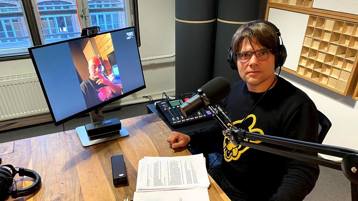 Junger Mann in einem Studio, auf einem Bildschirm sieht man seinen zugeschalteten Gesprächspartner