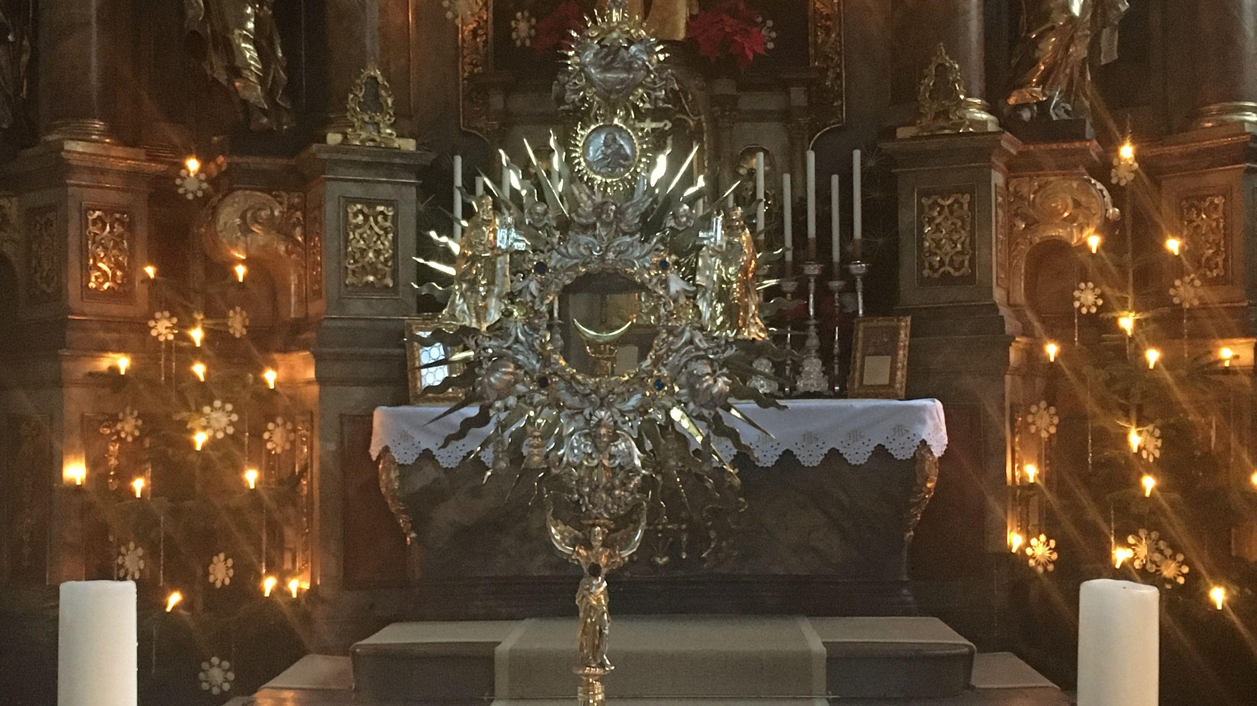In der Kirche St. Bartholomäus in Pottenstein steht vor dem Altar eine Montranz mit dem Allerheiligsten, daneben zwei Kerzen.