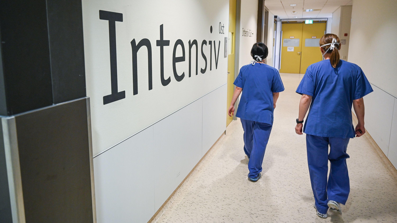 Zwei Pflegekräfte laufen auf dem Gang einer Intensivstation